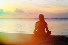 Woman meditation on the beach. Young woman meditation on sunset tropical beach Royalty Free Stock Photos