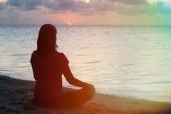 Woman meditation on the beach. Young woman meditation on sunset tropical beach Stock Photos