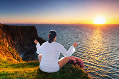 Woman at meditation on cliff Stock Photography
