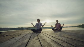 Woman meditation on the pier at the lake at sunset stock footage
