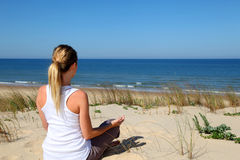 Woman in meditation pose making yoga Royalty Free Stock Image