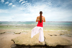 Woman in meditation on rock Royalty Free Stock Images