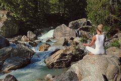 Woman meditation by a stream royalty free stock photo