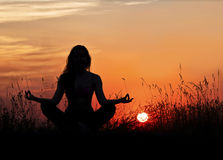 Woman in meditation on the street, amid zakata.yoga. Silhouette photo of woman in meditation on a background of a sunset landscape.yoga stock image