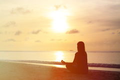 Woman meditation on sunset beach Royalty Free Stock Image