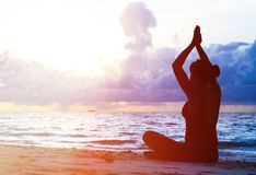 Woman meditation on sunset beach Royalty Free Stock Photo