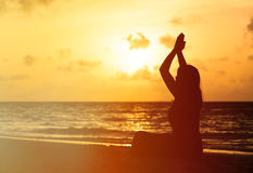 Woman meditation on sunset beach Stock Images
