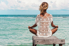 Woman meditation in a yoga pose at the beach Royalty Free Stock Photography