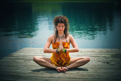 Woman in a meditative yoga position  by the lake Royalty Free Stock Photography