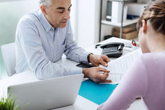 Woman meeting a consultant. Young women meeting a professional consultant in his office, he is holding a document and giving explanations Royalty Free Stock Images
