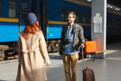 Woman meeting her boyfriend from his trip at the train station. Tourist Man with luggage and photo camers. Travel concept. Redhair Stock Photos