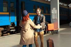 Woman meeting her boyfriend from his trip at the train station. Tourist Man with luggage and photo camers. Travel concept. Redhair Stock Photo