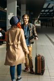 Woman meeting her boyfriend from his trip at the train station. Tourist Man with luggage and photo camers. Travel concept. Redhair Royalty Free Stock Photo