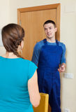 Woman meeting service worker at the door at home Royalty Free Stock Images
