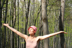 Woman meets sun in the forest. Adult woman dancing in the forest - blur royalty free stock photo