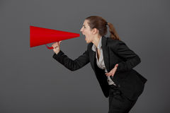 Woman with a megaphone. Business young woman speaking to a megaphone, over a grey background Stock Image