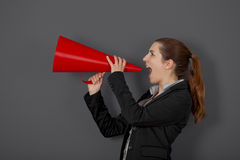 Woman with a megaphone. Business young woman speaking to a megaphone, over a grey background Stock Photography