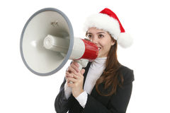 Woman with megaphone. Attractive young woman in Santa hat with megaphone at Christmas, white studio background Royalty Free Stock Images