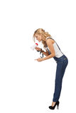 Woman with megaphone. Blonde woman shouts at someone small. Domination concept Royalty Free Stock Photography