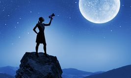 Woman with megaphone. Young woman speaking in megaphone against full moon Stock Photo