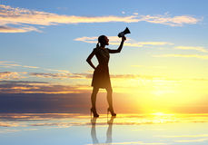 Woman with megaphone. Young woman speaking in megaphone against sunrise Stock Image