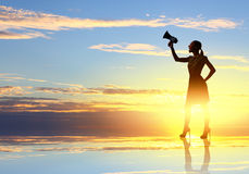 Woman with megaphone. Young woman speaking in megaphone against sunrise Stock Images