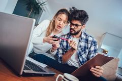Woman and man doing paperwork together, paying taxes online. Woman and men doing paperwork together, paying taxes online on laptop Royalty Free Stock Photo