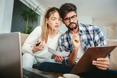 Woman and man doing paperwork together. Woman and men doing paperwork together, paying taxes online on notebook pc Royalty Free Stock Image