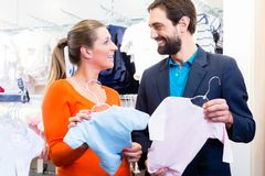 Woman and man expecting twins buying baby clothes. Woman and men expecting twins buying baby clothes, holding pink and blue suits for girl and boy royalty free stock photo