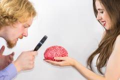 Couple using magnifying glass on human brain stock photo
