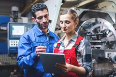 Woman and man manufacturing worker in discussion royalty free stock photography