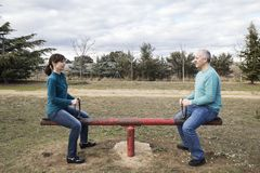 Woman and man mounted on a seesaw maintaining equality stock photos