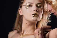 Woman and man relations. Golden collagen mask and beauty. 24K Gold. couple with golden body art makeup on stock photography