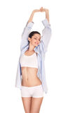 Woman in men's shirt stretching Stock Image