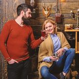 Woman and man on smiling faces enjoy cozy atmosphere with hot drinks. Couple spend pleasant evening, interior background stock images