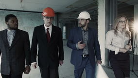 Woman, men in suit and helmet walk, discuss, communicate. Female with tablet is assistant director stock video footage