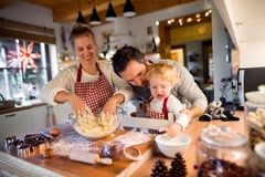 Young family making cookies at home. Woman, men and toddler boy making cookies at home. Mother, father and son baking gingerbread Christmas cookies Royalty Free Stock Photo