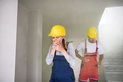 Woman and man workers running from the construction site, coughing. Woman and men workers running from the construction site, coughing and covering face royalty free stock photo
