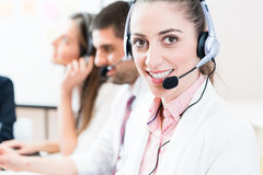 Woman and men working as call center agents stock photos