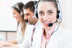 Woman and men working as call center agents Stock Photo