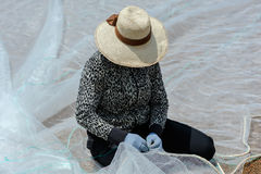 Woman mending fishing nets Royalty Free Stock Photos