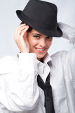 Woman in mens clothing. A pretty woman smiling in mens clothing and hat on white background Stock Image