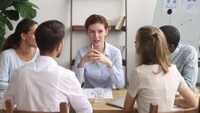 Diverse employees sitting around the table listening teacher receiving knowledge