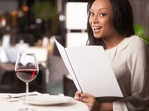Woman with a Menu. Beautiful African descent woman holding a Menu while sitting at the restaurant Stock Image