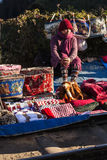 Woman merchant with coat and hood selling clothes on the ground in winter from Tiger Hill at Darjeeling, India Royalty Free Stock Photography