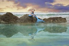 Mermaid at sea. A woman with a mermaid's tail sitting on a rock at sea stock image
