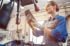 Woman in metal workshop checking workpiece Stock Photo