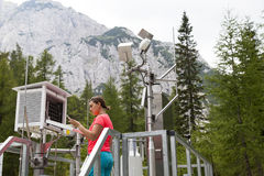 Woman meteorologist reading meteodata in mountain weather station Stock Photography