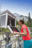 Woman meteorologist reading meteodata in mountain weather station Royalty Free Stock Image