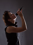 Woman with microphone. Young woman with microphone on gray background Royalty Free Stock Image